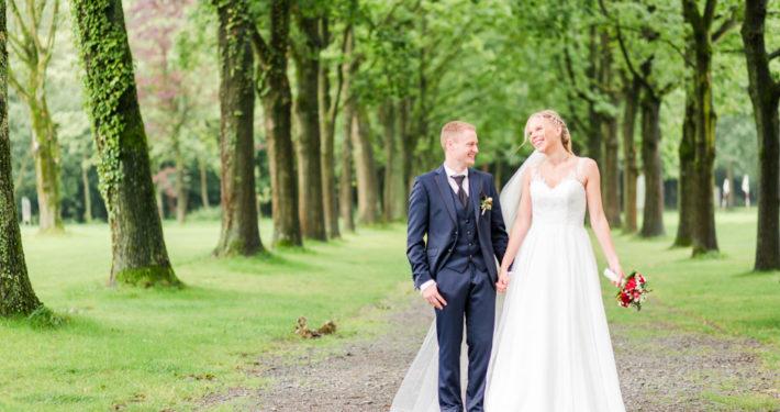 Brautpaar wandert eine Allee entlang auf Schloss Möhler