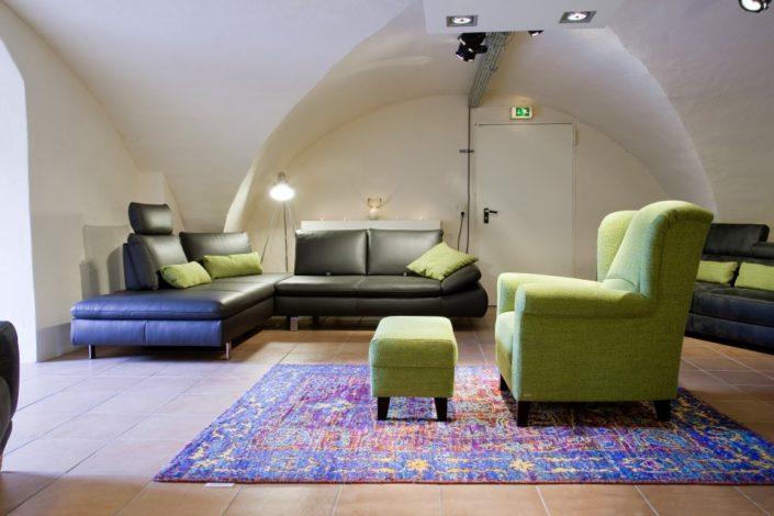 Grüner Einzelsessel und braune Leder-Sofas im Gewölbekeller der Location Schloss Möhler