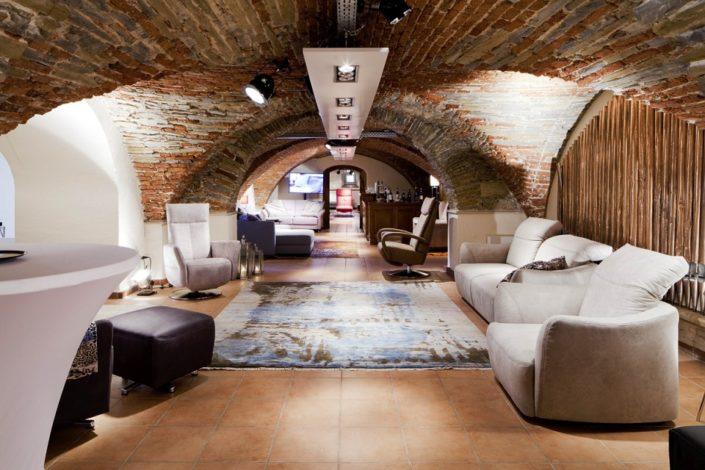 Blick bis auf roten Relaxsessel im Gewölbekeller der Location Schloss Möhler