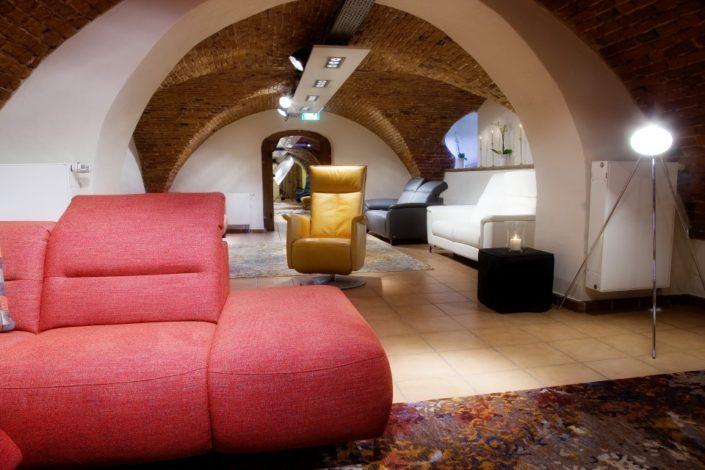 Gelber Einzelsessel und rote Sofas im Gewölbekeller der Location Schloss Möhler